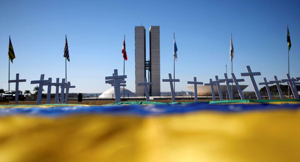 Mar de cruzes relembra as muitas mortes pela COVID-19 em frente ao Congresso Nacional em Brasília