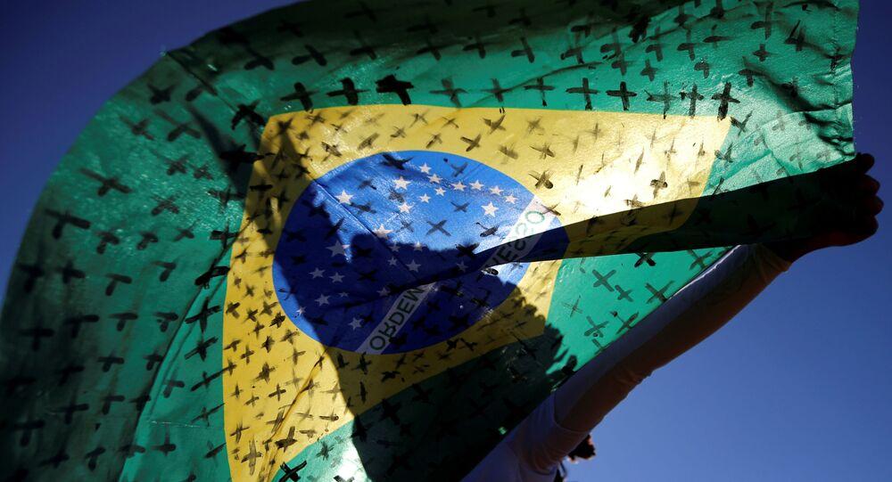 Ativista segura bandeira brasileira pintada com cruzes simbolizando os que morreram por COVID-19, durante protesto em frente ao Congresso Nacional, em Brasília, Brasil, 14 de julho de 2020