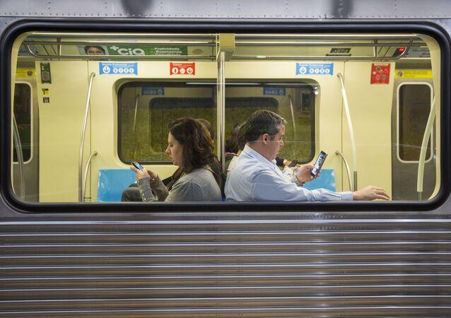 Passageiros usam o celular dentro do metrô de São Paulo