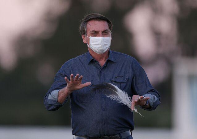 Presidente Jair Bolsonaro caminha no gramado do Palácio da Alvorada, em Brasília,  para acompanhar a cerimônia de descerramento da bandeira, que acontece na parte externa do jardim do Alvorada. Ele está em isolamento após ter sido diagnosticado com Covid-19, 15 de julho de 2020