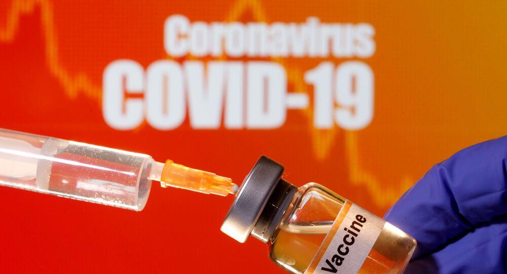 Pequeno frasco rotulado com um adesivo vacina é segurado perto de uma seringa médica na frente da mensagem Coronavírus COVID-19, 10 de abril de 2020