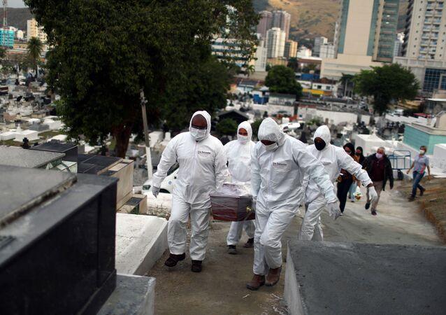 Funcionários de cemitério em Nova Iguaçu, no Rio de Janeiro, carregam caixão de vítima da COVID-19