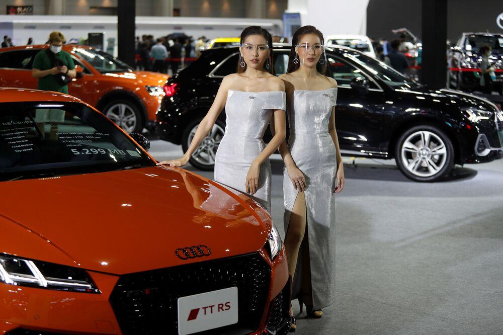 Modelos usam escudos faciais durante feira internacional de automóveis em Bangkok, Tailândia