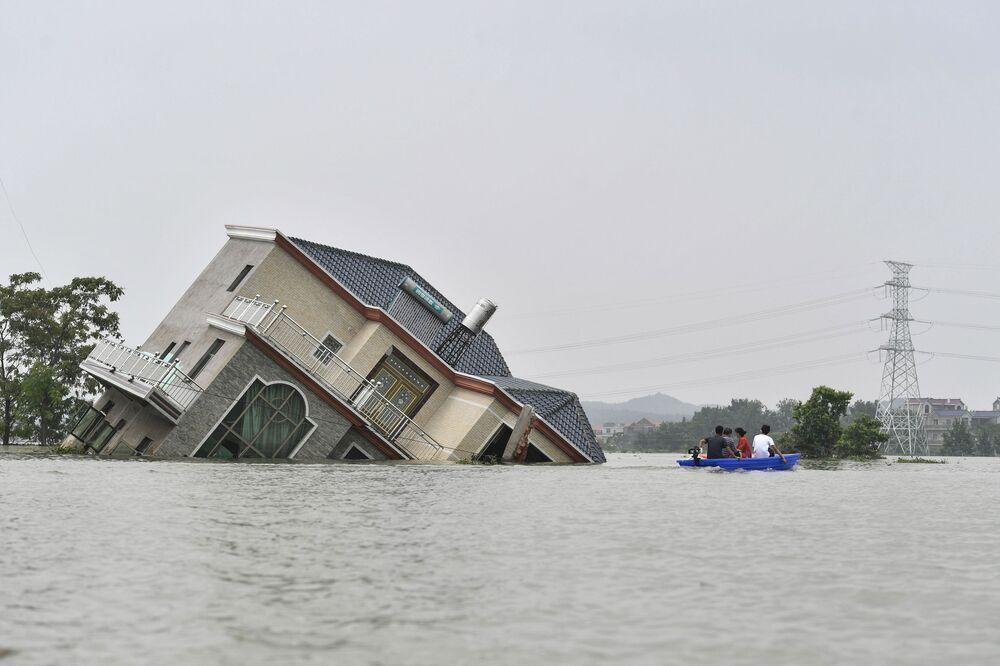 Casa tombada e inundada após chuvas torrenciais terem atingido o condado de Poyang, na China