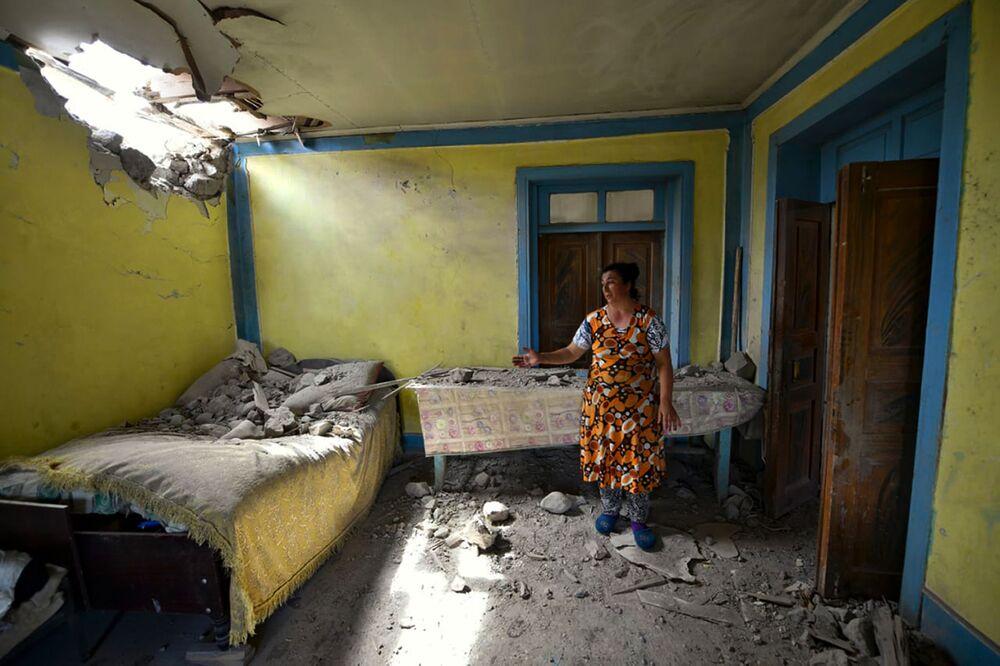 Mulher mostra estragos provocados por bombardeio efetuado por forças armênias contra a região de Tovuz, no Azerbaijão