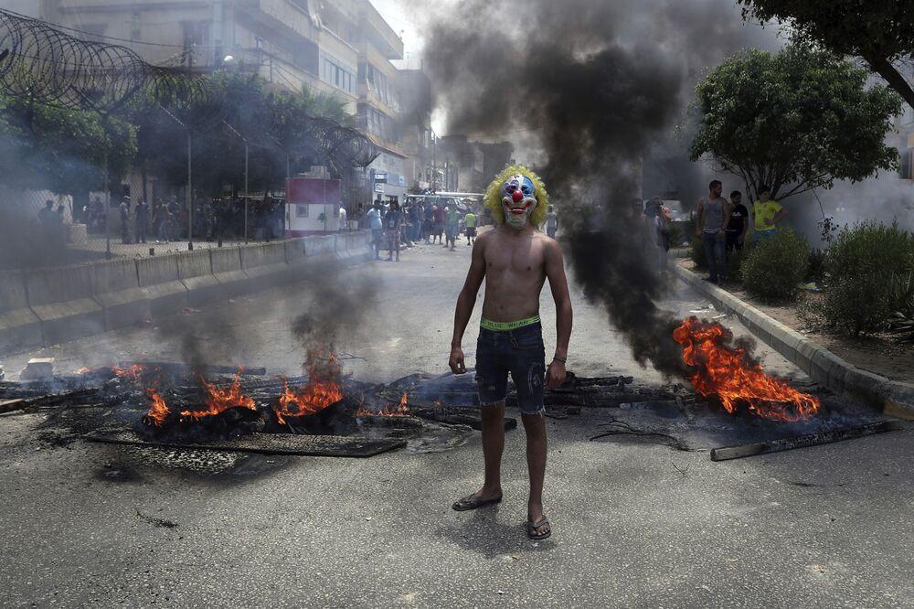 Homem usa máscara de palhaço para participar de protesto em Beirute contra o governo do Líbano