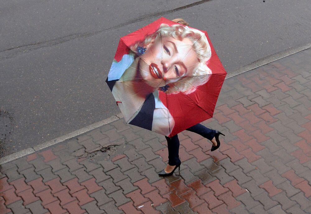 Mulher usa guarda-chuva com imagem da atriz americana Marylin Monroe na cidade russa de Krasnoyarsk