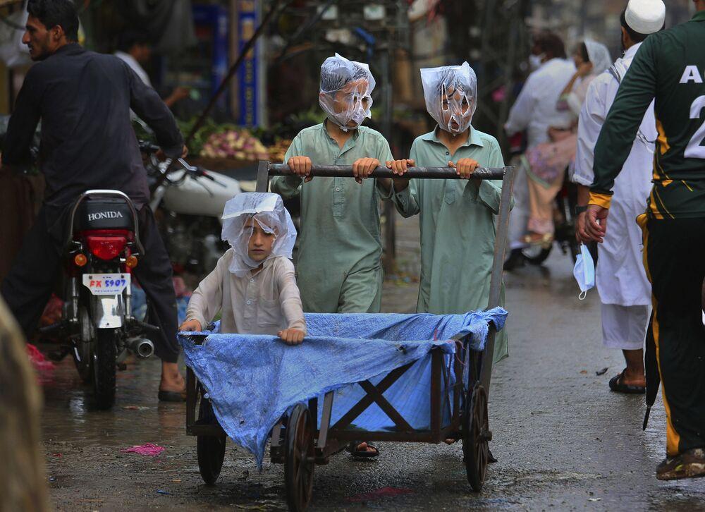 Crianças paquistanesas usam sacos plásticos para cobrirem suas cabeças durante a chuva em Peshawar, Paquistão