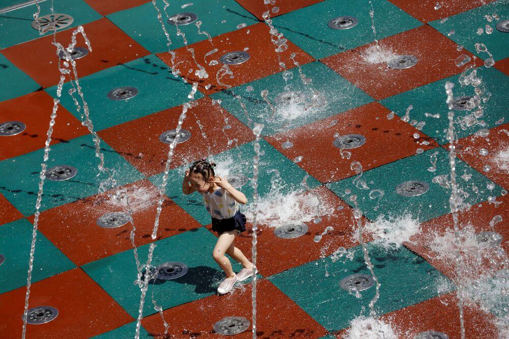 Menina brinca com a água em um dia de verão em um shopping de Pequim, China