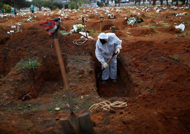 Funcionário do cemitério Vila Formosa, em São Paulo, enterra vítima da COVID-19 (coronavírus)