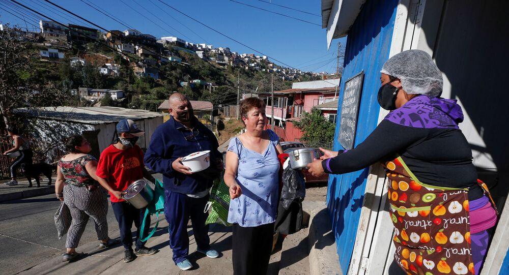 Voluntários distribuem comida em comunidade de Valparaiso, no Chile, atingida pela pandemia do coronavírus