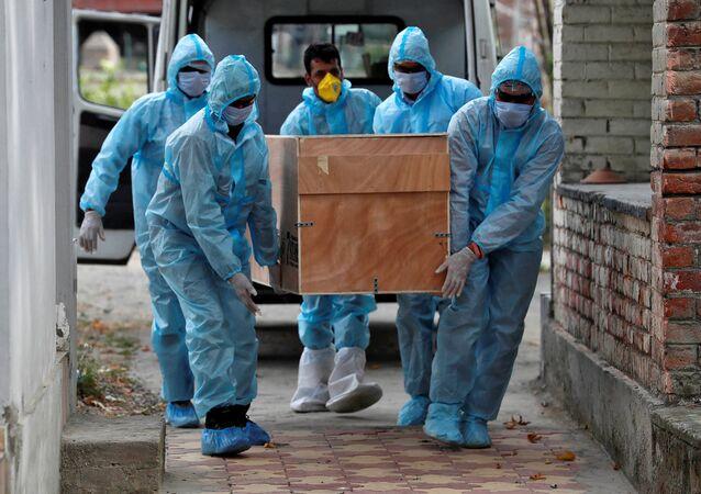 Profissionais da saúde carregam corpo de vítima da COVID-19 para cremação em Srinagar, Índia, 18 de julho de 2020