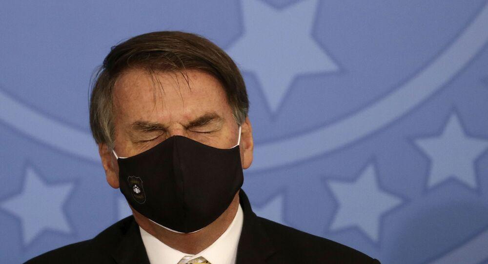 Em Brasília, durante evento, o presidente brasileiro, Jair Bolsonaro, aparece de olhos fechados e usando uma máscara durante a pandemia da COVID-19, em 15 de maio de 2020.