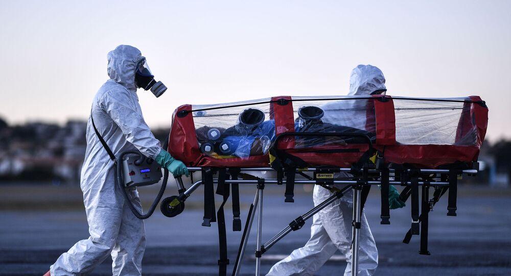Membros do Corpo de Bombeiros Militar do Estado de Minas Gerais, usando equipamento de proteção, carregam maca de isolamento para transportar pacientes com coronavírus, no Aeroporto da Pampulha, em Belo Horizonte (MG), Brasil, 22 de julho de 2020