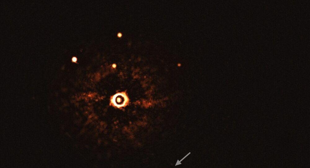 Imagem, capturada pelo instrumento SPHERE do telescópio VLT do Observatório Europeu do Sul (ESO, na sigla em inglês), mostra a estrela TYC 8998-760-1 acompanhada por dois exoplanetas gigantes, TYC 8998-760-1b e TYC 8998-760-1c