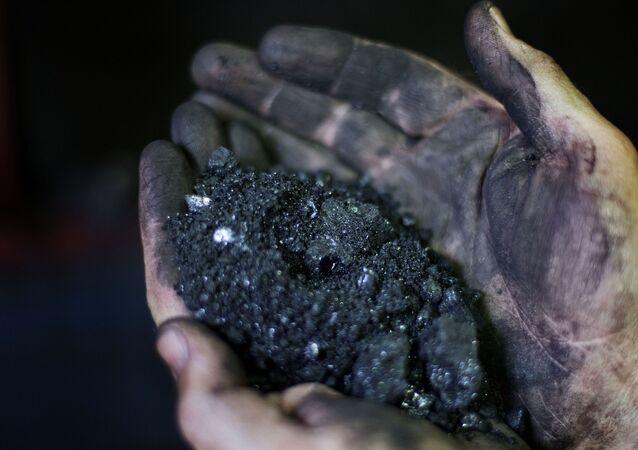 Pessoa segura minério em mina (imagem referencial)
