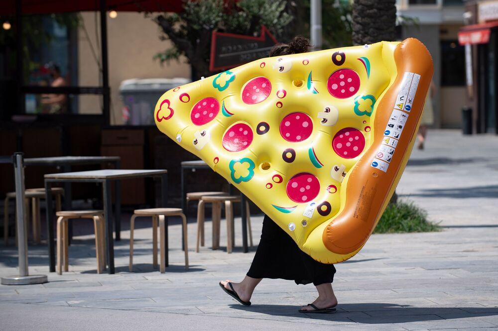 Mulher carrega pizza inflável pelas ruas de Barcelona, Espanha