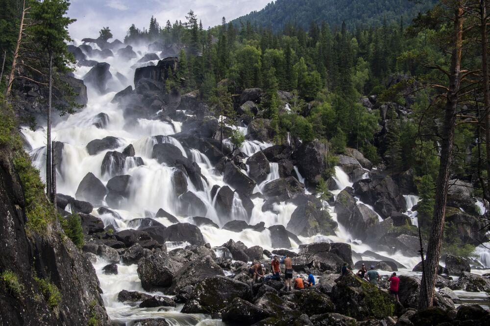 Homens contemplam a beleza da cascata Bolshoi Chulchinsky na república de Altai, Rússia