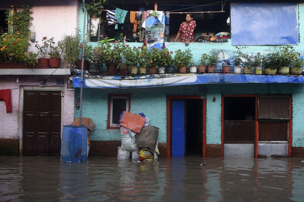 Mulher olha para rua durante enchente do rio Bagmati após fortes chuvas na capital do Nepal, Catmandu
