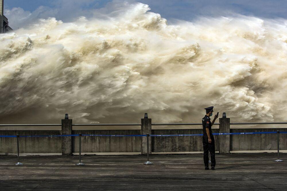 Guarda chinês é visto olhando para seu smartphone enquanto a usina hidrelétrica das Três Gargantas, uma das maiores do mundo, libera água em Yichang, na província chinesa de Hubei