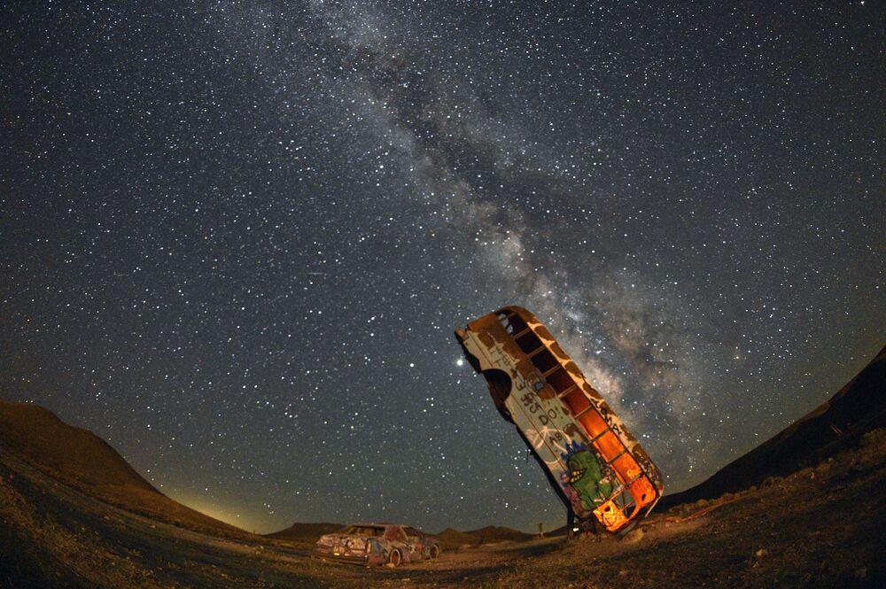 Ônibus é visto em zona de veículos abandonados no estado americano do Nevada, tendo ao fundo o esplendor da Via Láctea