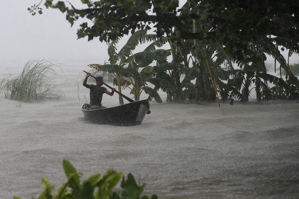 Homem rema durante forte chuva e inundação em Dohar, no Bangladesh