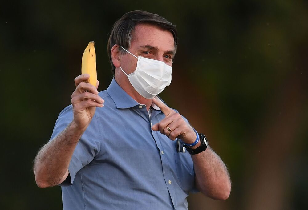 Presidente Jair Bolsonaro mostra banana para jornalistas enquanto vai ao encontro de apoiadores na parte de fora do Palácio da Alvorada