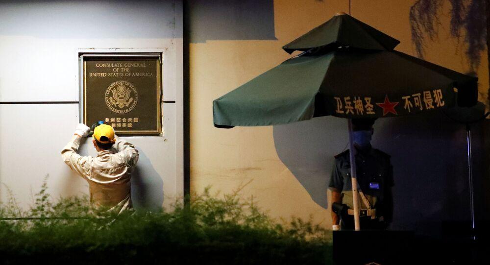 Homem retirada placa do consulado dos EUA em Chengdu, na China