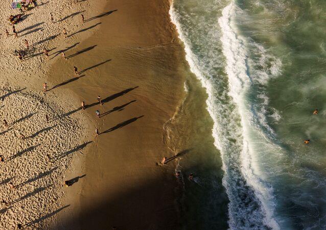 Pessoas são vistas na praia de Copacabana em meio à pandemia do coronavírus, no Rio de Janeiro, Brasil, 25 de julho de 2020