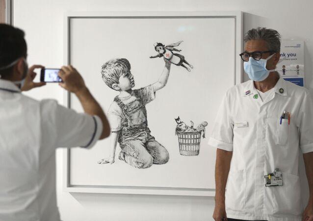 Um membro da equipe tira uma foto em frente à nova obra de arte pintada por Banksy durante o isolamento social, intitulada 'Game Changer', que foi exibida para funcionários e pacientes no Nível C do Hospital Geral de Southampton, em Southampton, Inglaterra, durante maio de 2020.