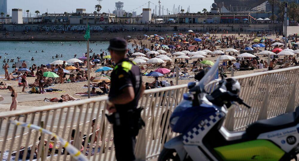 Policial observa praia lotada de turistas e espanhóis durante a COVID-19 em Barcelona