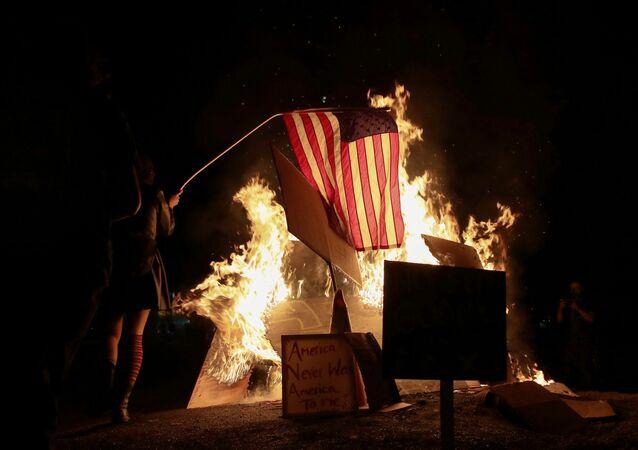 Manifestante põe fogo em bandeira americana durante protesto contra a desigualdade racial e a violência policial em Portland, Oregon, EUA, 27 de julho de 2020