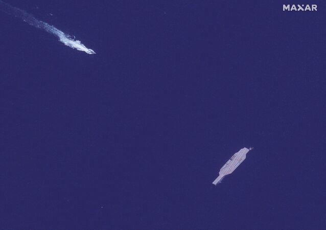 Maquete de porta-aviões americano, usada como alvo durante um exercício de jogos de guerra naval do Irã, é abordada por uma lancha rápida no estreito de Ormuz, 26 de julho de 2020