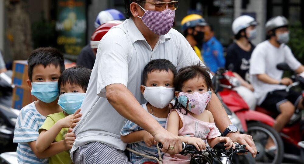 Homem e crianças, com máscaras protetoras, andam de bicicleta na rua em meio à pandemia do coronavírus, em Hanói, Vietnã, 27 de julho de 2020