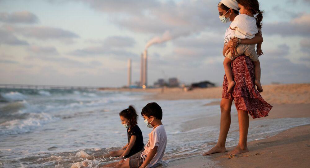 Crianças usando máscaras brincam na água ao longo da costa do mar Mediterrâneo ao visitarem a praia de Zikim, em meio à disseminação do coronavírus, no sul de Israel, 21 de julho de 2020