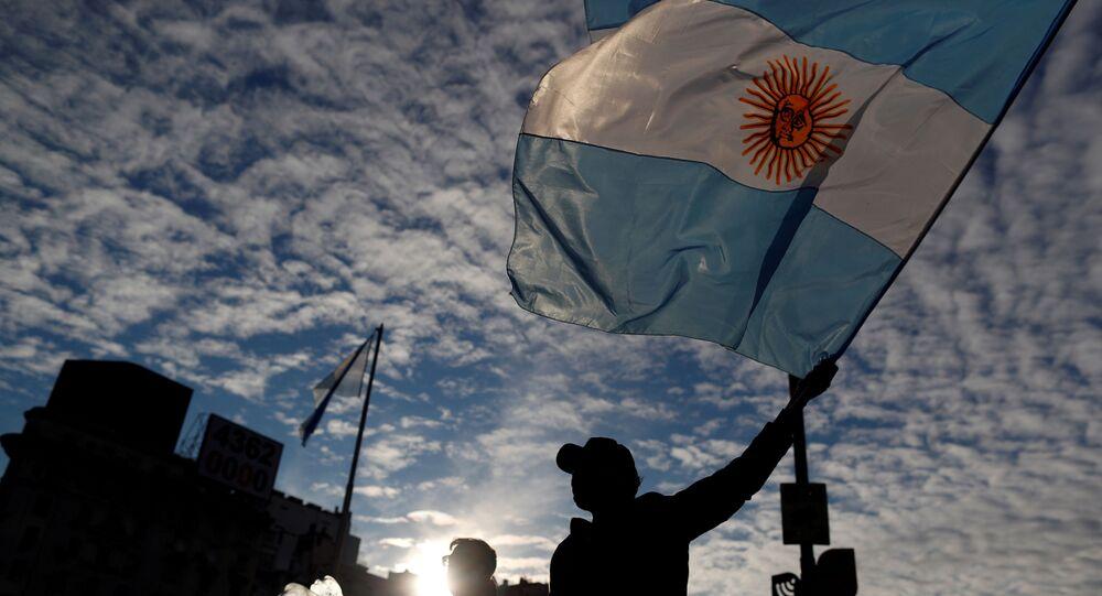 Homem segura a bandeira da Argentina durante protesto que pedia a flexibilização da quarentena imposta no país em razão da pandemia da COVID-19.
