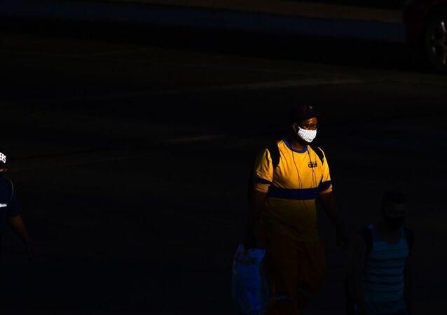 Homem caminha de máscara em Brasília, no Distrito Federal.