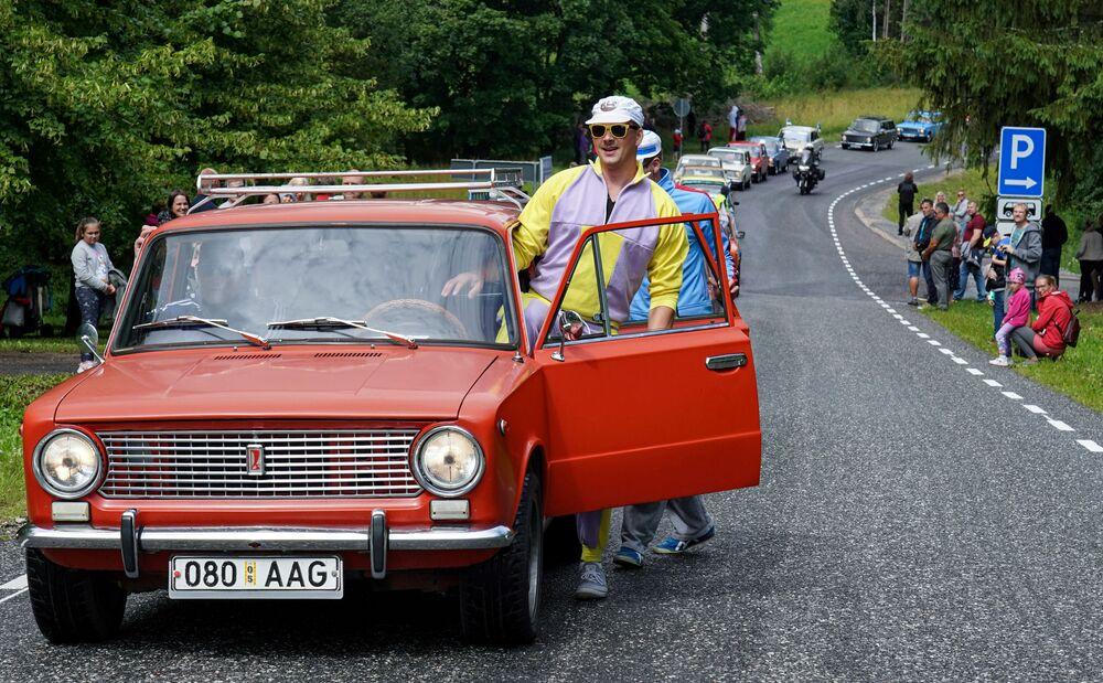Homem entra em carro Lada durante parada de aniversário dos 50 anos da marca em Varbuse, Estônia