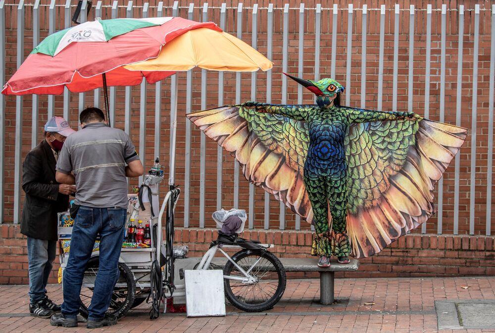 Pessoa se veste de colibri em Bogotá, Colômbia, para incentivar população local a respeitar as medidas contra a pandemia da COVID-19