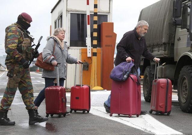 Soldado belga acompanha passageiros em aeroporto de Zaventem, nos arredores de Bruxelas (arquivo)