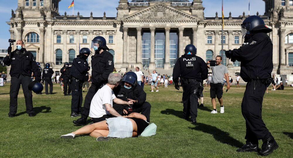Em Berlim, no dia 1º de agosto de 2020, um policial conversa com manifestantes, perto do Reichstag ,durante protesto contra medidas de restrição social impostas pelo governo.