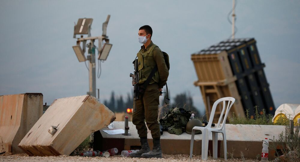 Soldado israelense em frente a um sistema anti-míssil da Cúpula de Ferro nas proximidades da fronteira com o Líbano
