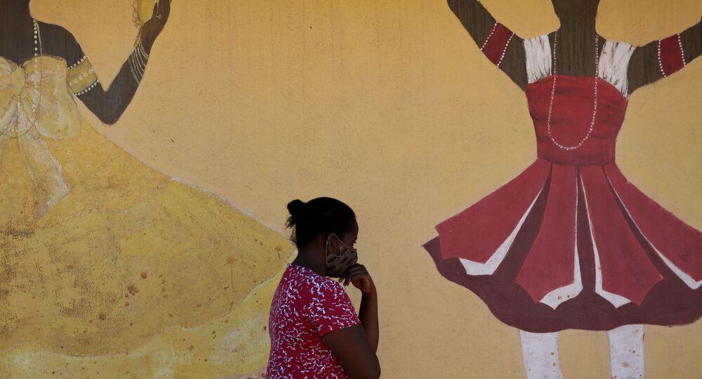 Pedestre passa por muro pintado com figuras de orixás, na comunidade do Sol Nascente, em Brasília, 2 de agosto de 2020