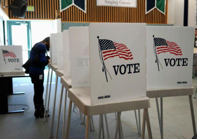 Em Westminster, no estado do Colorado, EUA, um eleitor deposita seu voto em uma urna durante as eleições legislativas norte-americanas, em 4 de novembro de 2014.