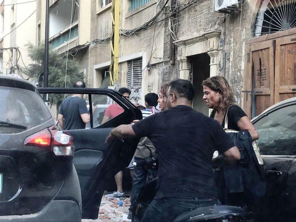 Pessoas feridas por fragmentos de vitrines são socorridas após uma explosão perto do porto de Beirute