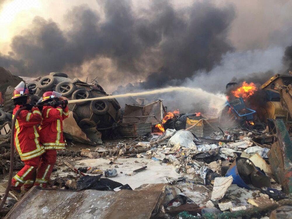 Bombeiros jogam água para combater o fogo oriundo de uma explosão na região portuária de Beirute