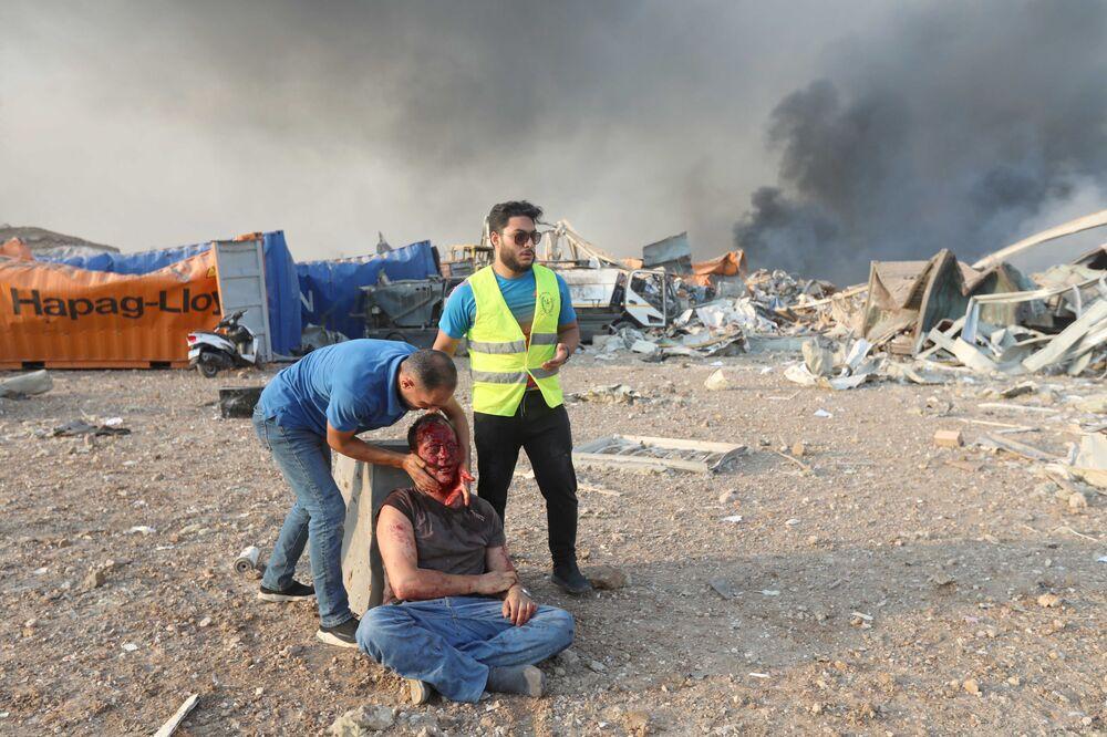 Homem ferido recebe assistência no local de uma explosão na região portuária de Beirute