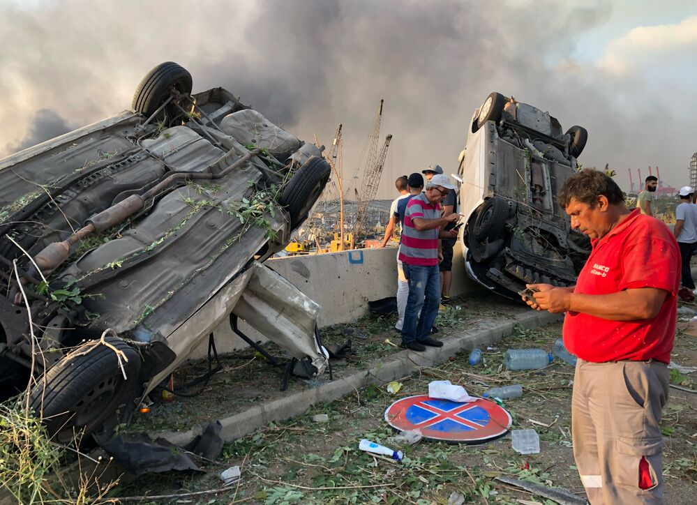 Pessoas se posicionam próximas a carros destruídos pela explosão em Beirute