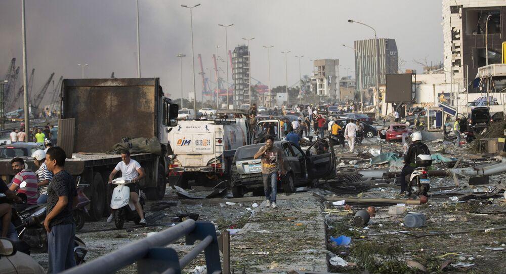 Em Beirute, pessoas circulam entre carros e destroços em rodovia após forte explosão na zona portuária da capital libanesa que causou destruição pela cidade, em 4 de agosto de 2020.