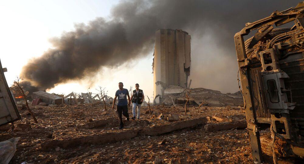 Em Beirute, dois homens caminham no local de uma grande explosão ocorrida na capital libanesa em 4 de agosto de 2020.